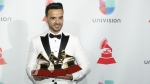 Luis Fonsi poses in the press room with the awards for best urban/ fusion/performance, best short form music video and record of the year for 'Despacito' at the 18th annual Latin Grammy Awards at the MGM Grand Garden Arena in Las Vegas on Thursday, Nov. 16, 2017. (Eric Jamison / Invision)