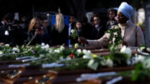 A woman places flowers on coffins during the funeral service for 26 Nigerian women, at the Salerno cemetery, southern Italy, Friday Nov.17, 2017. (Alessandra Tarantino/AP Photo)