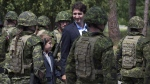 Prime Minister Justin Trudeau and his son Xavier review an honour guard as they arrive at the International Peacekeeping and Security Centre in Yavoriv, Ukraine Tuesday July 12, 2016. (Adrian Wyld/The Canadian Press)