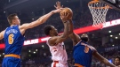Toronto Raptors guard DeMar DeRozan, centre, shoots against New York Knicks forward Kristaps Porzingis (6) and centre Kyle O'Quinn (9) during first half NBA basketball action in Toronto on Friday, November 17, 2017. THE CANADIAN PRESS/Chris Young