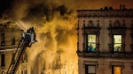 A woman watches through the window of her apartment as firefighters battle a large fire on the top floors of an apartment building in New York City's Harlem neighborhood, Friday, Nov. 17, 2017. (AP / Andres Kudacki)
