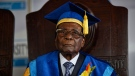 Zimbabwe's President Robert Mugabe sits for formal photographs with university officials, after presiding over a student graduation ceremony at Zimbabwe Open University on the outskirts of Harare, Zimbabwe Friday, Nov. 17, 2017. Mugabemade his first public appearance since the military put him under house arrest earlier this week. (AP Photo/Ben Curtis)