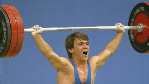 In this Tuesday Sept. 20, 1988 file photo, Naim Suleymanoglu of Turkey yells it out during one of the lifts which won him a gold medal in the 60-kilogram Olympic weightlifting competition at the Summer Olympics in Seoul, South Korea. (AP Photo/Kang Hyoung, File)