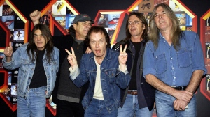 A March 3, 2003 file photo of from left: Malcolm Young, Brian Johnson, Angus Young, Phil Rudd and Cliff Williams from AC/DC posing for photographers at the Apollo Hammersmith in London. The band has announced, Saturday Nov. 18, 2017, that 64-year-old Young has died. (Yui Mok/PA via AP)