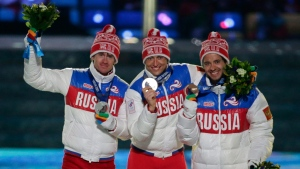 FILE- In this Sunday, Feb. 23, 2014 file photo, from left, Russia's silver medal winner Maxim Vylegzhanin, Russia's gold medal winner Alexander Legkov and Russia's bronze medal winner Ilia Chernousov pose during the medals ceremony for the men's 50K cross-country race during the closing ceremony of the 2014 Winter Olympics in Sochi, Russia. (AP Photo/Charlie Riedel)