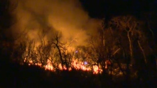 A brush fire burning near Shaganappi Point Golf Course early Saturday morning