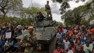 Army soldiers stand guard as protesters demanding President Robert Mugabe stands down gather on the road leading to State House in Harare, Zimbabwe Saturday, Nov. 18, 2017. (AP / Ben Curtis)