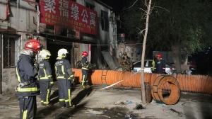 In this photo provided by China's Xinhua News Agency, firefighters work at the site of a fire in Daxing district of Beijing, capital of China, Sunday, Nov. 19, 2017. (Xinhua/Luo Xiaoguang)