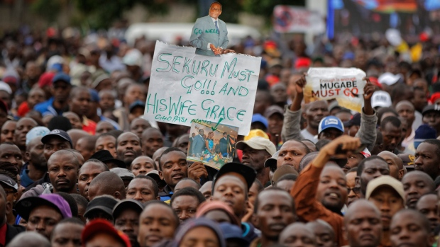 """A protester holds a banner referring to President Mugabe as """"grandfather"""", at a demonstration at Zimbabwe Grounds in Harare, Zimbabwe Saturday, Nov. 18, 2017. Opponents of Mugabe are demonstrating for the ouster of the 93-year-old leader who is virtually powerless and deserted by most of his allies. (AP Photo/Ben Curtis)"""
