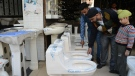 An Indian shopworker shows toilets to customers on the eve of the 'World Toilet Day' in a hardware shop in Amritsar on Nov. 18, 2017 (NARINDER NANU / AFP)