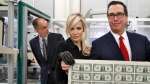 Treasury Secretary Steven Mnuchin, right, and his wife Louise Linton, hold up a sheet of new $1 bills, the first currency notes bearing his and U.S. Treasurer Jovita Carranza's signatures, Wednesday, Nov. 15, 2017, at the Bureau of Engraving and Printing (BEP) in Washington. (AP Photo/Jacquelyn Martin)