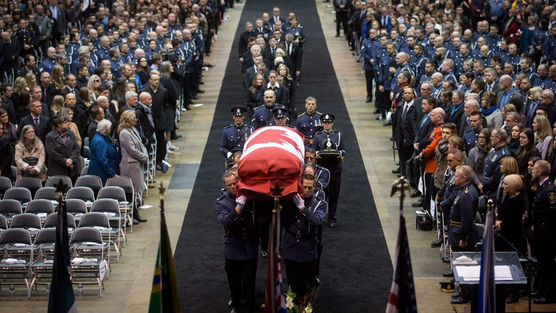 Pallbearers carry the casket of Abbotsford Police Const. John Davidson, who was killed in the line of duty on November 6, into a memorial service in Abbotsford, B.C., on Sunday November 19, 2017. (THE CANADIAN PRESS/Darryl Dyck)