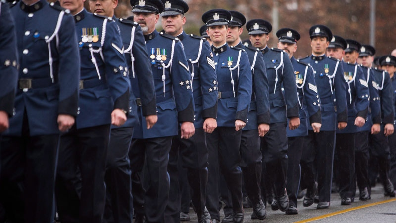 Abbotsford Police Officers walk in formation behind the funeral procession carrying the body of Abbotsford Police Const. John Davidson, who was killed in the line of duty on Nov. 6, on their way to a memorial in Abbotsford, B.C., on Sunday November 19, 2017. (THE CANADIAN PRESS/Ben Nelms)