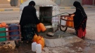 FILE - A Thursday Oct. 19, 2017 file photo of women filling up containers with water from a hose, in Zagora, southeastern Morocco. (AP Photo/Issam Oukhouya)