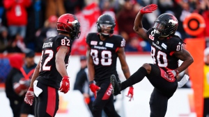 Calgary Stampeders' Juwan Brescacin (82) and Kamar Jorden (88) celebrate with Marken Michel (80) who scored a touchdown against the Edmonton Eskimos during second quarter CFL West Final football action in Calgary, Sunday, Nov. 19, 2017. (Todd Korol/The Canadian Press)