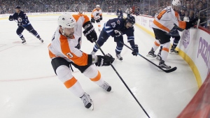 Philadelphia Flyers' Radko Gudas (3) picks up the puck in his corner as Winnipeg Jets' Mathieu Perreault (85) covers the pass during second period NHL action, in Winnipeg, on Saturday, Nov. 7, 2015. (THE CANADIAN PRESS/John Woods)