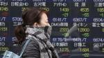 A woman walks by an electronic stock board of a securities firm in Tokyo, Monday, Nov. 20, 2017. (AP / Koji Sasahara)