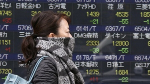 A woman walks by an electronic stock board of a securities firm in Tokyo, Monday, Nov. 20, 2017. (AP / Koji Sasahara)