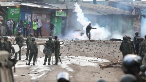 A supporter of opposition leader Raila Odinga throws back a canister of tear gas towards riot police during running battles with police in Kibera Slums in Nairobi, Kenya, Sunday, Nov. 19, 2017. (AP / Brian Inganga)