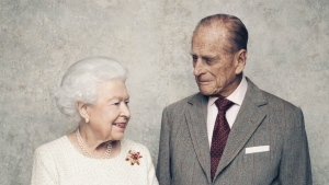 Queen Elizabeth II and Prince Philip pose for a photograph in the White Drawing Room pictured against a platinum-textured backdrop at Windsor Castle, England in this photo taken in Nov. 2017. (Matt Holyoak / Camera Press)