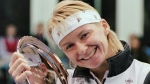In this Nov. 17, 1996 photo, Jana Novotna, of the Czech Republic, is all smiles after taking home a $79,000 check from the Advanta Tennis Championship in Villanova, Pa. (AP Photo/Jim Graham)