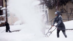 People clear snow from their sidewalks and streets after a large amount of snow fell in Toronto on Monday, February 2, 2015. THE CANADIAN PRESS/Nathan Denette