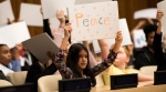 Children hold up drawings reading Peace ahead of Monday's event to mark World Children's Day at the United Nations Headquarters. (Susan Markisz/ UNICEF)