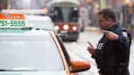A police constable speaks to a taxis driver during the second day of the King Street Transit Pilot involving city streetcars on Monday, November 13, 2017. THE CANADIAN PRESS/Doug Ives