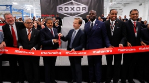 Anand G. Mahindra, Chairman, Mahindra Group, third from left, participates with Michigan Lt. Gov. Brian Calley, fourth from left, in a ceremonial ribbon butting in Auburn Hills, Mich., Monday, Nov. 20, 2017. (AP Photo/Paul Sancya)