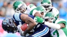 Toronto Argonauts running back James Wilder Jr. (32) is wrapped up by Saskatchewan Roughriders defenders during first half CFL Eastern final action, Sunday, November 19, 2017 in Toronto. THE CANADIAN PRESS/Frank Gunn