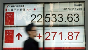 A man walks past an electronic stock board showing Japan's Nikkei 225 index at a securities firm in Tokyo Tuesday, Nov. 21, 2017. (AP / Eugene Hoshiko)