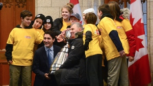 Prime Minister Justin Trudeau and CFL commissioner Randy Ambrosie join The Tigers, a youth flag football team from Orleans. Ont., for a photo with the Grey Cup outside the Prime Ministers office on Parliament Hill in Ottawa on Nov. 21, 2017. THE CANADIAN PRESS/Sean Kilpatrick