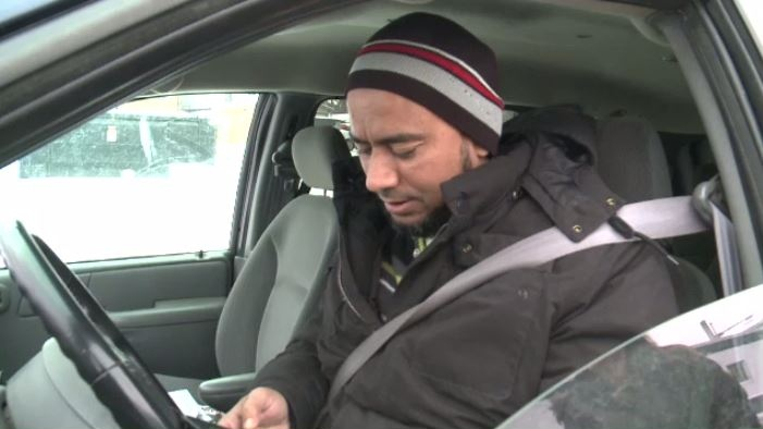 Taxi driver Ahmed Araf compares gas prices online before filling up at the pump