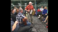 """A group of people waiting for a flight at Pearson International Airport take part in an impromptu """"Kitchen Party"""" Monday November 20, 2017.  (Michelle Sacrey Philpott /Facebook)"""