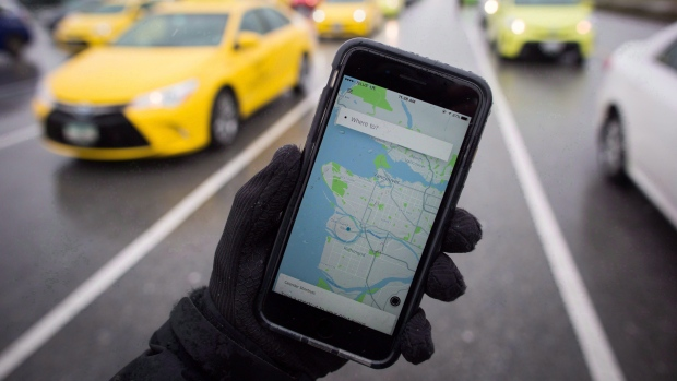 The Uber app is displayed on an iPhone as taxi drivers wait for passengers at Vancouver International Airport, in Richmond, B.C., on Tuesday, March 7, 2017. (THE CANADIAN PRESS / Darryl Dyck)