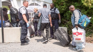 A group of asylum seekers cross the Canadian border at Champlain, N.Y., Friday, August 4, 2017. THE CANADIAN PRESS/Ryan Remiorz