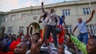 Zimbabweans celebrate outside the parliament building immediately after hearing the news that President Robert Mugabe had resigned, in downtown Harare, Zimbabwe Tuesday, Nov. 21, 2017. Mugabe resigned as president with immediate effect Tuesday after 37 years in power, shortly after parliament began impeachment proceedings against him. (AP Photo/Ben Curtis