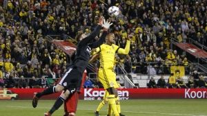 Toronto FC's Alex Bono, left, makes a save over Columbus Crew's Ola Kamara during the first half of an MLS Eastern Conference championship soccer match in Columbus, Ohio on Tuesday, Nov. 21, 2017. (AP / Jay LaPrete)