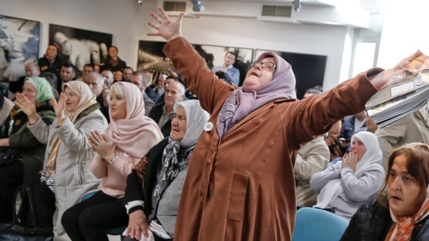 Ediba Salihovic, right, stands up and raises her hands as she reacts along with other Bosnian women upon hearing the sentence at the end of former Bosnian Serb military chief Gen. Ratko Mladic's trial at the memorial center in Potocari, near Srebrenica, Bosnia, Wednesday, Nov. 22, 2017. (AP Photo/Amel Emric)