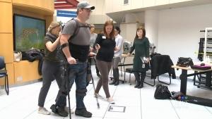 Ryan Nicoll walks with the help of an Ekso exoskeleton at Glenrose Rehabilitation Hospital in Edmonton, Alta., on Nov. 21, 2017.