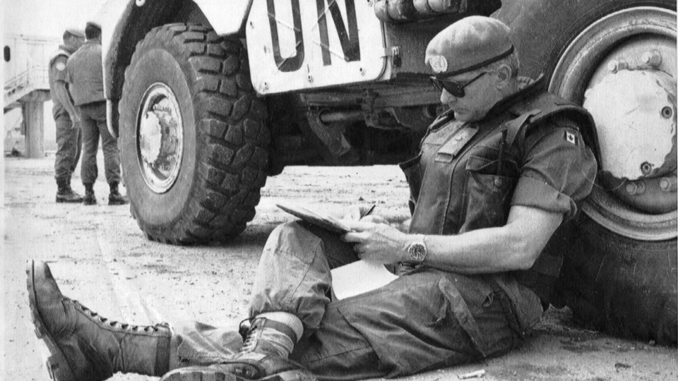 In this file photo, retired Maj. Gen. Lewis MacKenzie does paperwork behind an armoured personnel carrier on the tarmac at Sarajevo Airport on June 30, 1992. (Morten Hvaal/AP)