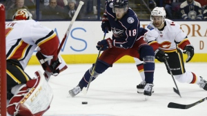 Columbus Blue Jackets' Pierre-Luc Dubois, centre, looks for an open shot as Calgary Flames' TJ Brodie, right, defends during the second period of an NHL hockey game in Columbus, Ohio on Wednesday, Nov. 22, 2017. (AP / Jay LaPrete)