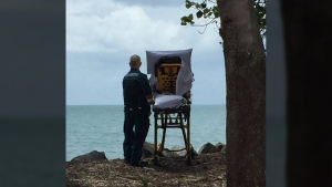 A paramedic stands with a palliative care patient near the beach at Hervey Bay, in Queensland, Australia. (Queensland Ambulance Service / Facebook)