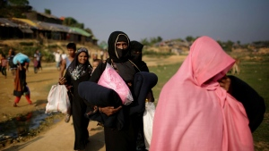 "FILE - In this Tuesday, Nov. 21, 2017, file photo, Rohingya Muslim women carry blankets and other supplies they collected from aid distribution centers in Kutupalong refugee camp in Bangladesh. The United States declared the ongoing violence against Rohingya Muslims in Myanmar to be ""ethnic cleansing"" on Wednesday, Nov. 22, putting more pressure on the country's military to halt a brutal crackdown that has sent more than 600,000 refugees flooding over the border to Bangladesh. (AP Photo/Wong Maye-E, File)"