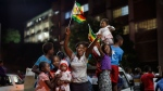 Zimbabweans celebrate at night at an intersection in downtown Harare, Zimbabwe Tuesday, Nov. 21, 2017. Mugabe resigned as president with immediate effect Tuesday after 37 years in power, shortly after parliament began impeachment proceedings against him. (AP Photo/Ben Curtis)