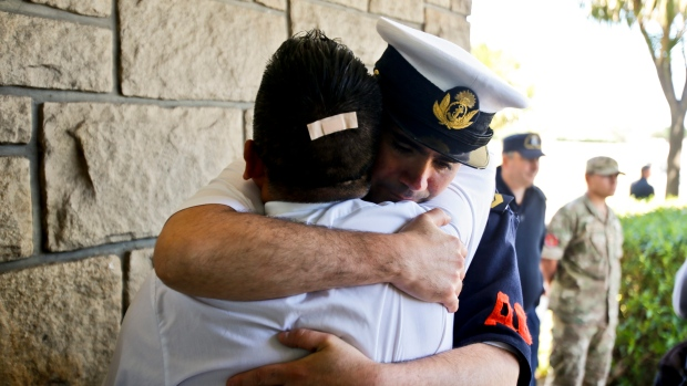 Argentine Navy officials embrace inside the Mar de Plata Naval Base after Argentina's Navy announced that a sound detected during the search for the missing ARA San Juan submarine is consistent with that of an explosion, in Mar de Plata, Argentina, Thursday, Nov. 23, 2017. (AP Photo/Esteban Felix)