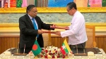 In this image provided by Myanmar's Ministry of Information, Myanmar's Union Minister for the Office of the State Counsellor Kyaw Tint Swe, right, and Bangladesh Foreign Minister Abdul Hassan Mahmud Ali exchange notes after signing the Arrangement on Return of Displaced Persons from Rakhine State in Naypyitaw, Myanmar, Thursday, Nov. 23, 2017. Myanmar and Bangladesh signed an agreement on Thursday covering the return of Rohingya Muslims who fled across their mutual border to escape violence in Myanmar's Rakhine state. (Myanmar Information Ministry via AP)