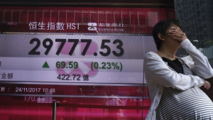 A woman walks past a bank electronic board showing the Hong Kong share index at Hong Kong Stock Exchange Friday, Nov. 24, 2017. (AP / Vincent Yu)