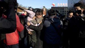 A woman leaves with a child after telling the media she came to withdraw the child from the RYB kindergarten in Beijing, China on Friday, Nov. 24, 2017. (AP / Ng Han Guan)