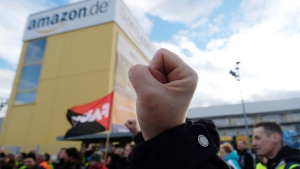 A participant of a demonstration raises his fist in front of the local site of the online retail company Amazon in Leipzig, Germany, Friday, Nov. 24 2017. (Sebastian Willnow / dpa)